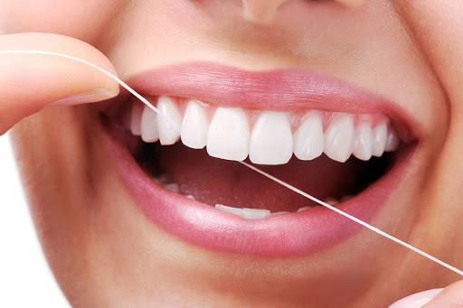 dental patient flossing their teeth